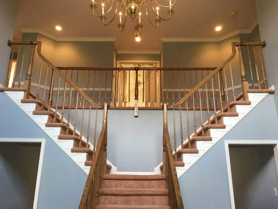 Grand foyer with a double staircase painted with a finish.